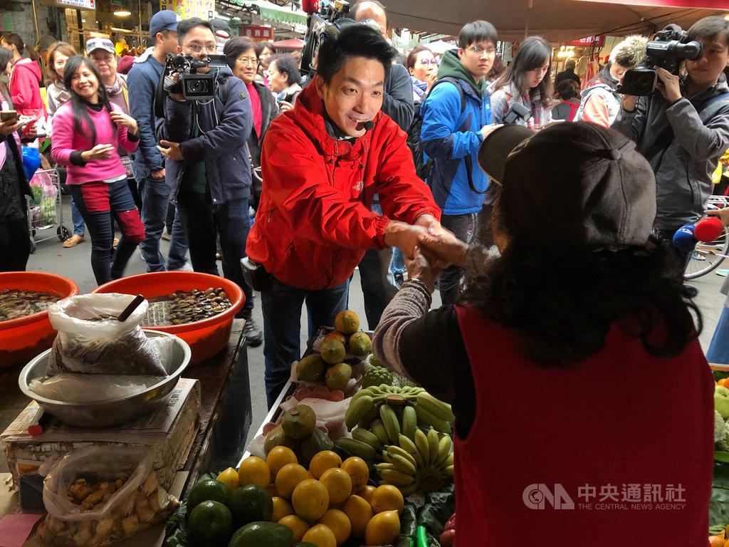國民黨立委蔣萬安19日前往台北市草埔市場謝票,緊握攤販的手。他也表態未規劃參選黨主席,但絕不缺席黨的改造工程。中央社記者王承中攝 109年1月19日