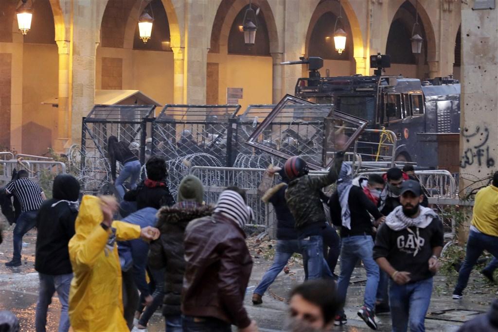 黎巴嫩首都貝魯特18日爆發警民衝突,安全部隊出動水柱並發射催淚瓦斯驅離示威者,造成雙方共220多人受傷。(美聯社)