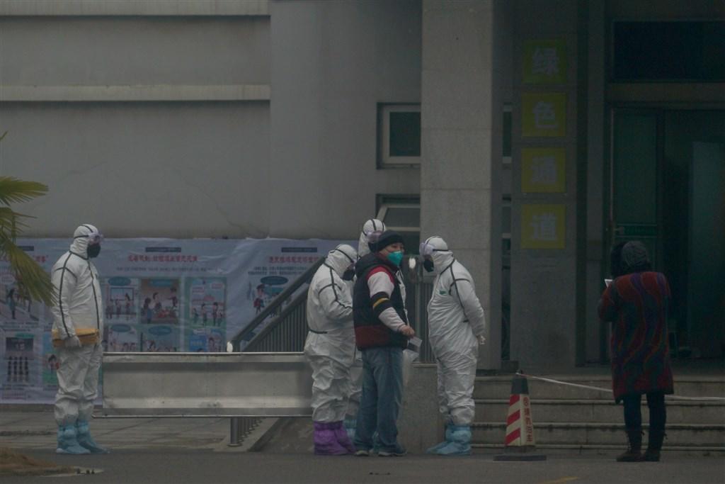 中國官方22日舉行記者會通報武漢肺炎疫情,截至21日晚上12時,中國共13省出現疫情,共確診440例。圖為武漢醫療救治中心外,醫護人員穿著防護隔離衣。(美聯社)