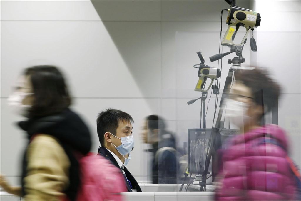 防範武漢肺炎,日本口罩需求增加,廠商接獲各地業者追加口罩的訂單,被迫趕工生產。圖為關西機場旅客及檢疫人員。(共同社提供)