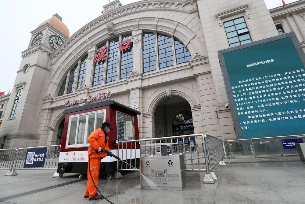 武漢肺炎疫情擴散,當地23日上午10時開始暫停公共運輸,無特殊原因不得離開武漢。圖為中國漢口火車站工作人員23日在站前廣場消毒。(中新社提供)