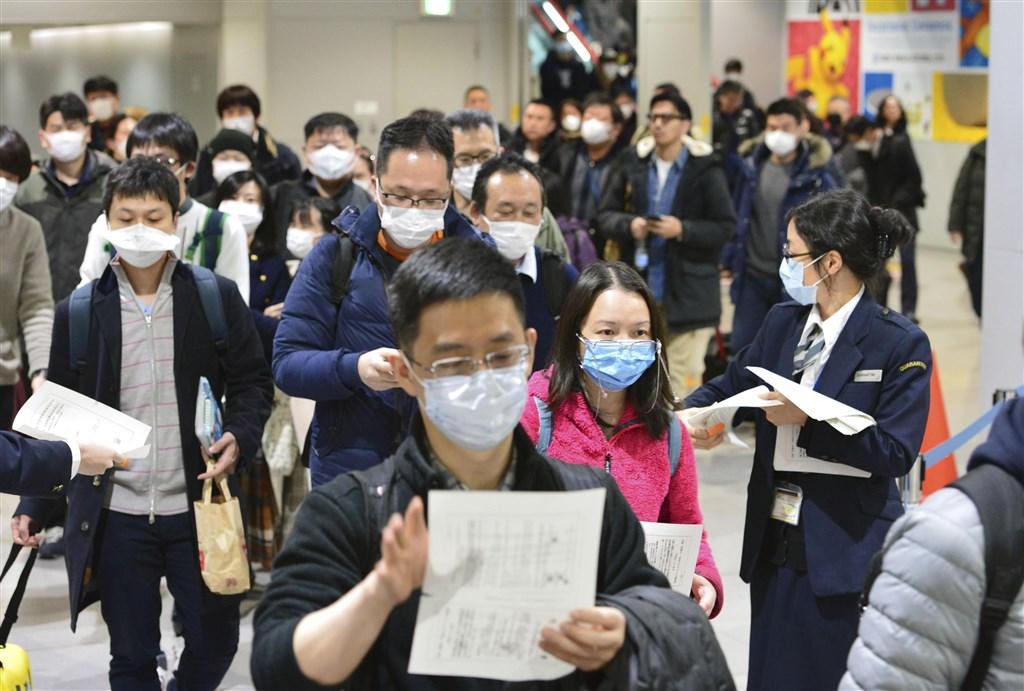 為因應武漢肺炎,日本外務省官網今天將中國湖北省全境「傳染病危險情報」等級,從等級2提升至等級3。圖為日本關西機場發放健康宣傳單給從中國入境的旅客。(共同社提供)