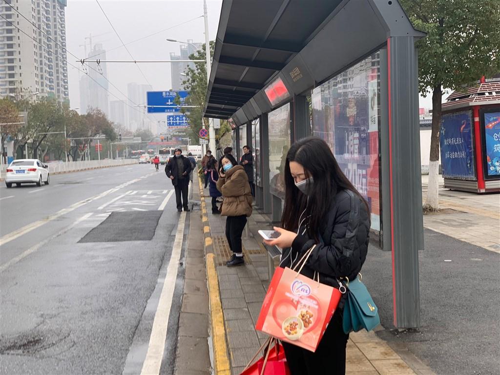 中國武漢大學人民醫院發布報告指出,有些武漢肺炎的患者一開始並沒有典型的發燒、咳嗽、乏力症狀,增加了診斷難度和傳染機會。圖為23日武漢市民眾戴口罩等候公車。(中新社提供)