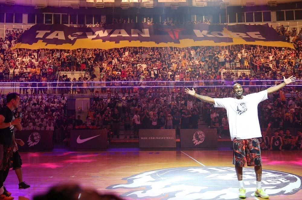美國職籃NBA洛杉磯湖人傳奇球星布萊恩(前右)生前5度造訪台灣,還曾在訓練營指導台灣年輕球員。圖為布萊恩2015年來台出席籃球訓練營畫面。(中央社檔案照片)
