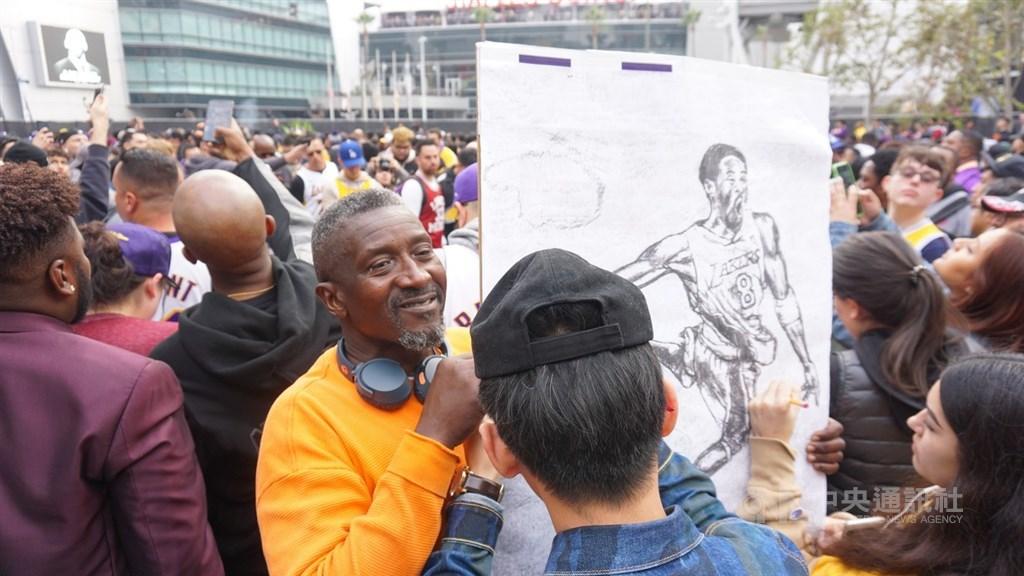 美國職籃NBA洛杉磯湖人傳奇球星布萊恩(Kobe Bryant)26日過世,球迷聚集在湖人主場史泰博中心(Staples Center)外的廣場,追思紀念他。一名球迷拿著手繪的布萊恩畫像,供路人留言,寫下對布萊恩的思念。中央社記者林宏翰洛杉磯攝 109年1月27日