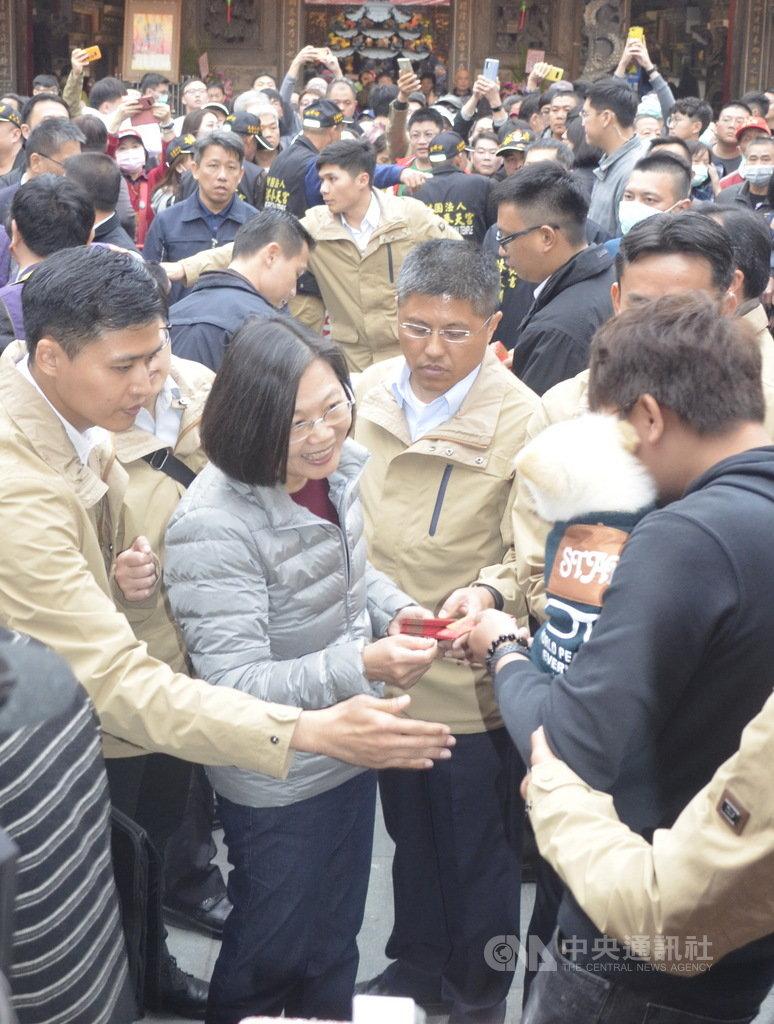 總統蔡英文27日在新港奉天宮發福袋,一位民眾抱著寵物狗狗來領福袋,總統流露欣喜的表情。中央社記者蔡智明攝 109年1月27日