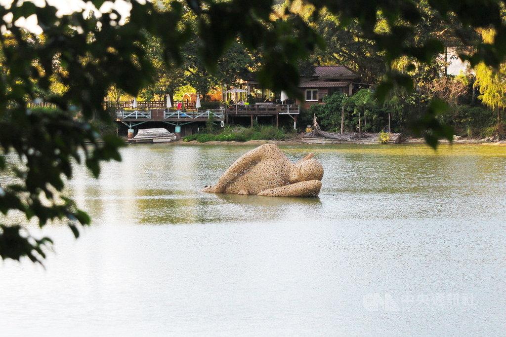 新竹縣政府邀6名印尼藝術家在峨眉鄉十二寮大埤湖中打造地景藝術,其中竹編打造半躺半臥人像「懶散時光」寓意是提醒觀看者善待自然。中央社記者郭宣彣攝 109年1月28日