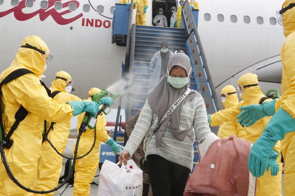 印尼政府的撤僑專機2日返抵巴淡島,自湖北省返國的國人下機後先噴灑消毒液,再搭軍機接駁至納土納縣的軍醫院隔離觀察。(印尼外交部提供)中央社記者石秀娟雅加達傳真 109年2月2日