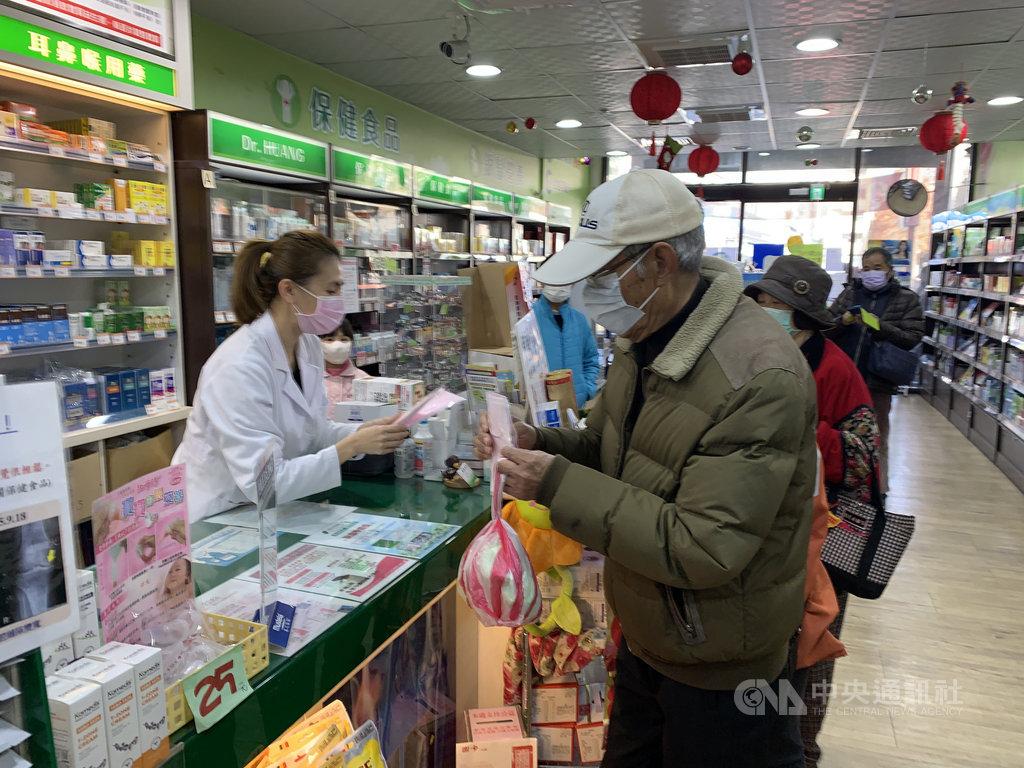 口罩實名制6日上路,藥師向民眾收健保卡過卡並收取現金後給予口罩,過程十分快速。中央社記者葉臻攝 109年2月6日