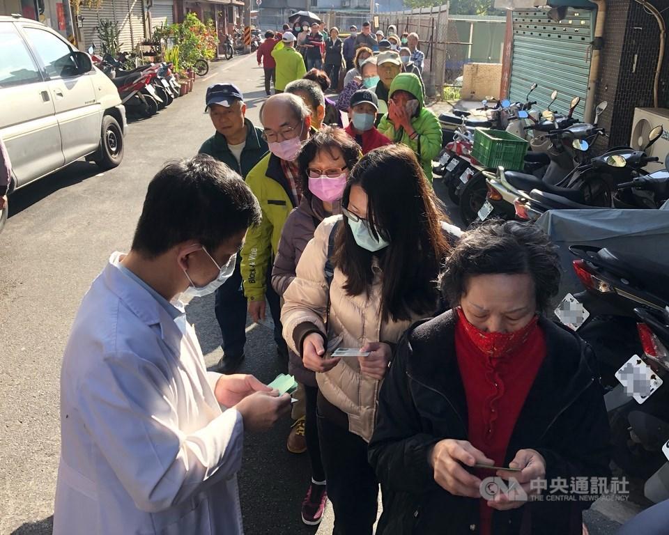 中國武漢肺炎疫情引發口罩搶購潮,口罩實名制6日上路,台北市一家藥局一早就有民眾在外等候,還未開門就大排長龍,藥劑師發放號碼牌給排隊民眾。中央社記者王飛華攝 109年2月6日