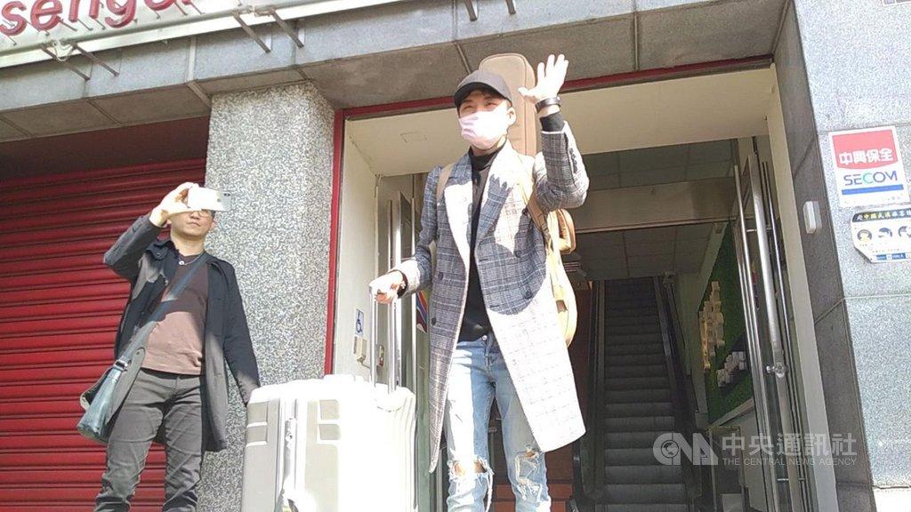 麗星郵輪寶瓶星號日前獲准返回基隆港,在船上駐唱的星光一班出身歌手劉明峰(右)13日上午戴著口罩、背吉他下船。中央社記者王朝鈺攝  109年2月13日