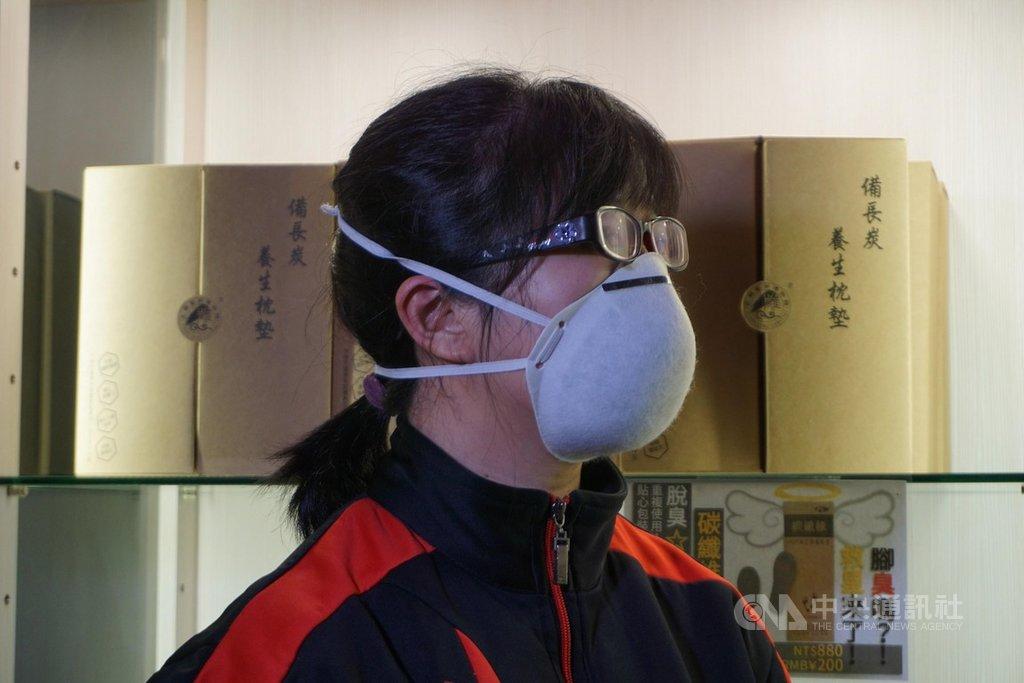 金門一家業者準備1000個高科技碳纖維口罩,15、16日兩天分送給民眾。業者示範這款口罩鬆緊帶是從前往後戴,也可將2條繩子同時往後套,讓口罩更緊貼口鼻。中央社記者黃慧敏攝  109年2月14日