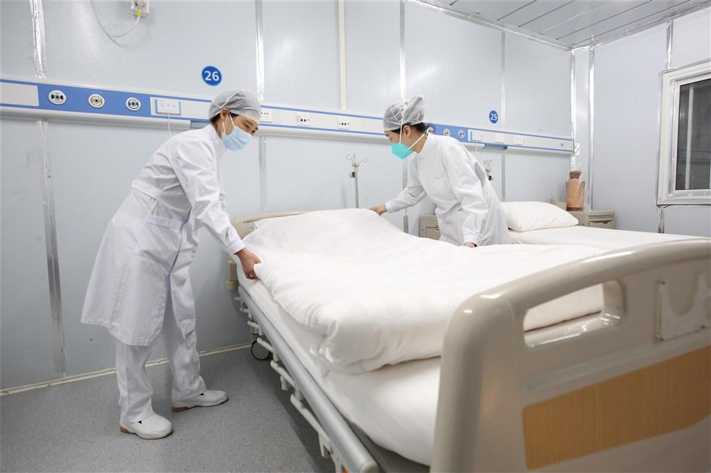 中國湖北省衛生健康委員會官網14日通報,2月13日新增武漢肺炎確診病例4823例,比12日新增確診病例數大減超過1萬。圖為武漢雷神山醫院醫護人員整理病房。(中新社提供)