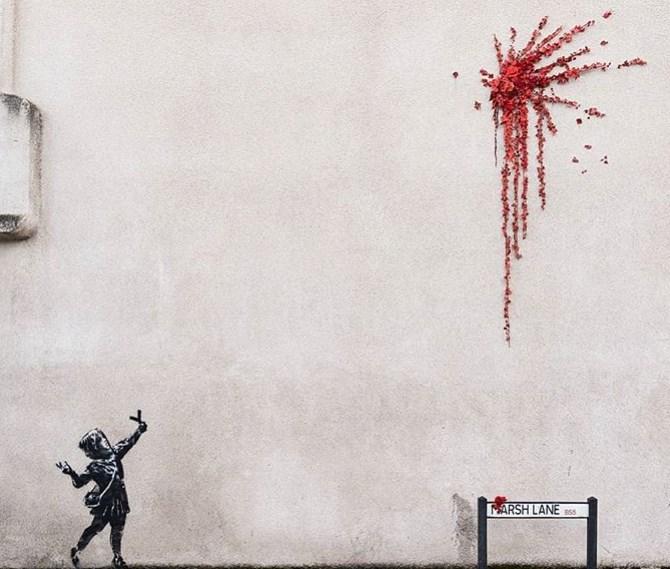 英國知名塗鴉藝術家班克西送給家鄉布里斯托一份情人節禮物,畫中可見一名小女孩手持彈弓射出一簇紅花煙火。(圖取自班克西IG網頁instagram.com/banksy)