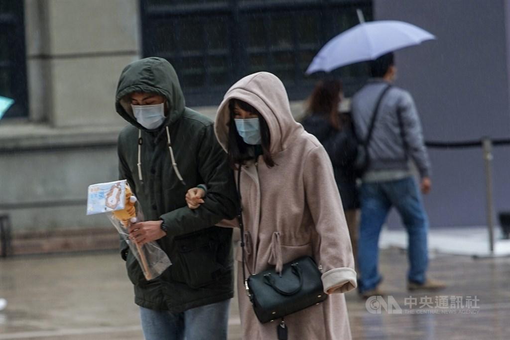 寒流報到,中央氣象局16日上午發布最新低溫特報,受影響範圍擴大,從原本10縣市增加至17縣市,可能出現攝氏10度左右或以下氣溫。下午台北市區開始降雨,出遊民眾戴起帽子遮雨。中央社記者裴禛攝 109年2月16日