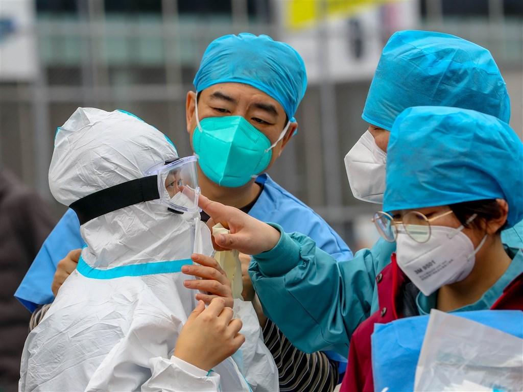武漢肺炎疫情快速蔓延,不到一個月時間,全球五大洲全都出現確診案例。圖為武漢江岸塔子湖方艙醫院醫護人員進入醫院前做好防護措施。(中新社提供)