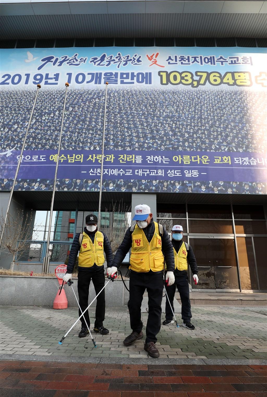 南韓21日通報新增52例武漢肺炎確診病例,其中與新天地大邱教會有關者共39人。圖為防疫人員於新天地大邱教會消毒。(韓聯社提供)