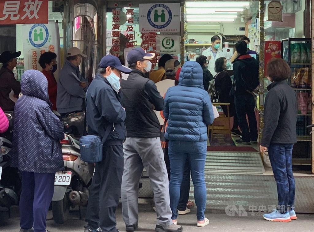 武漢肺炎疫情嚴峻,台灣自6日起實施口罩販售實名制,20日仍可見許多民眾在藥局門口排隊等待購買。中央社記者張新偉攝 109年2月20日