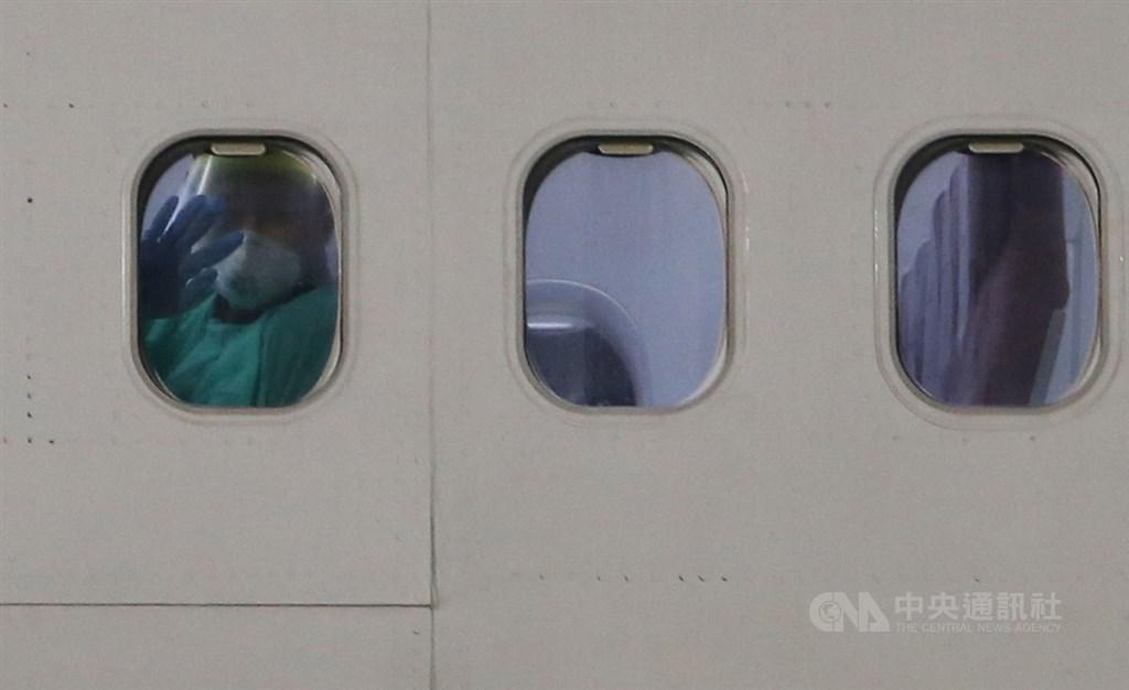 台灣派出包機接回日本郵輪鑽石公主號上台籍旅客及先遣醫師,21日晚間順利返台,機內穿著隔離衣的旅客透過機窗向外揮手致意。中央社記者邱俊欽桃園機場攝 109年2月21日