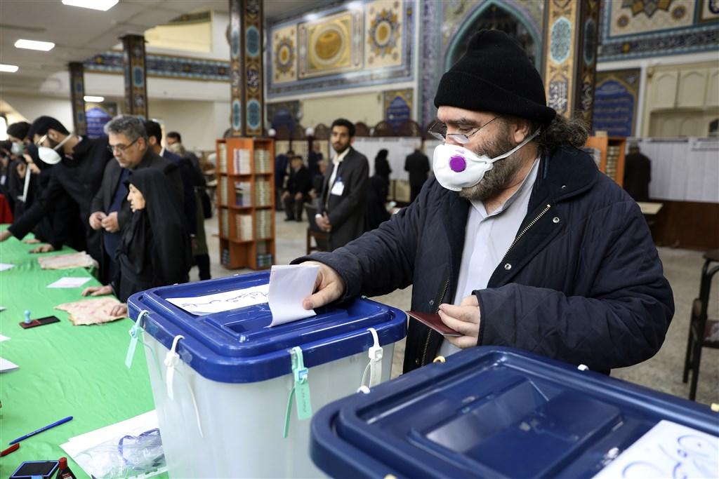 伊朗21日新增13起武漢肺炎確診病例,其中2人已經死亡。圖為伊朗議會選舉,選民戴口罩投票。(美聯社)