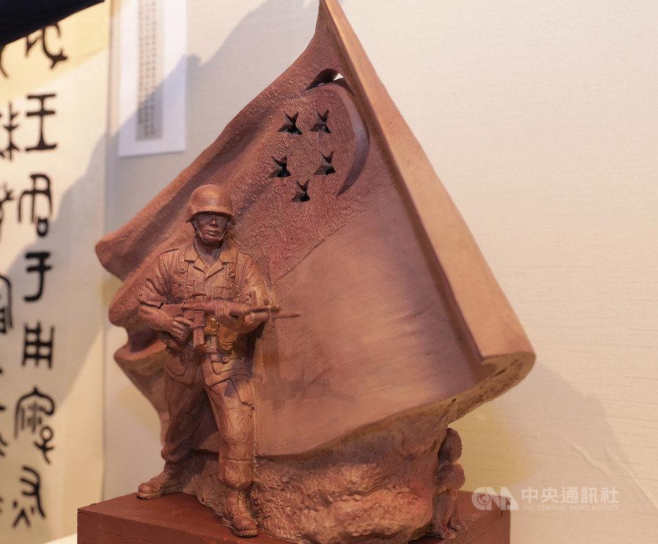 新加坡德光島軍人持槍站在飄揚國旗下蓄勢待發的巨型雕塑,是台灣雕塑家陳連山作品,圖為陳連山展出這座原創版「國民服役」雕塑模型。中央社記者黃自強新加坡攝 109年2月21日