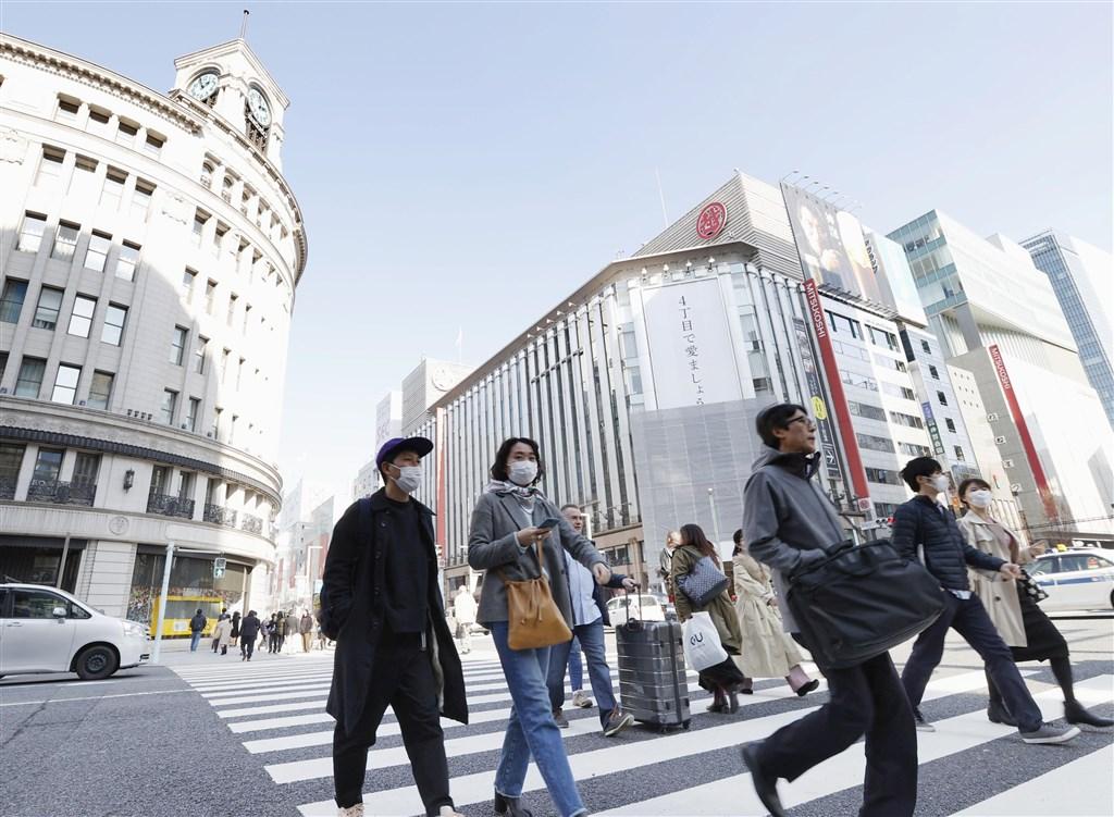 中央流行疫情指揮中心22日將日本及韓國升級至旅遊疫情第二級,旅遊業者說,先前日韓疫情升溫時,旅遊團就約已退了一半,預期未來還可能退更多。圖為東京銀座街頭民眾戴口罩。(共同社提供)