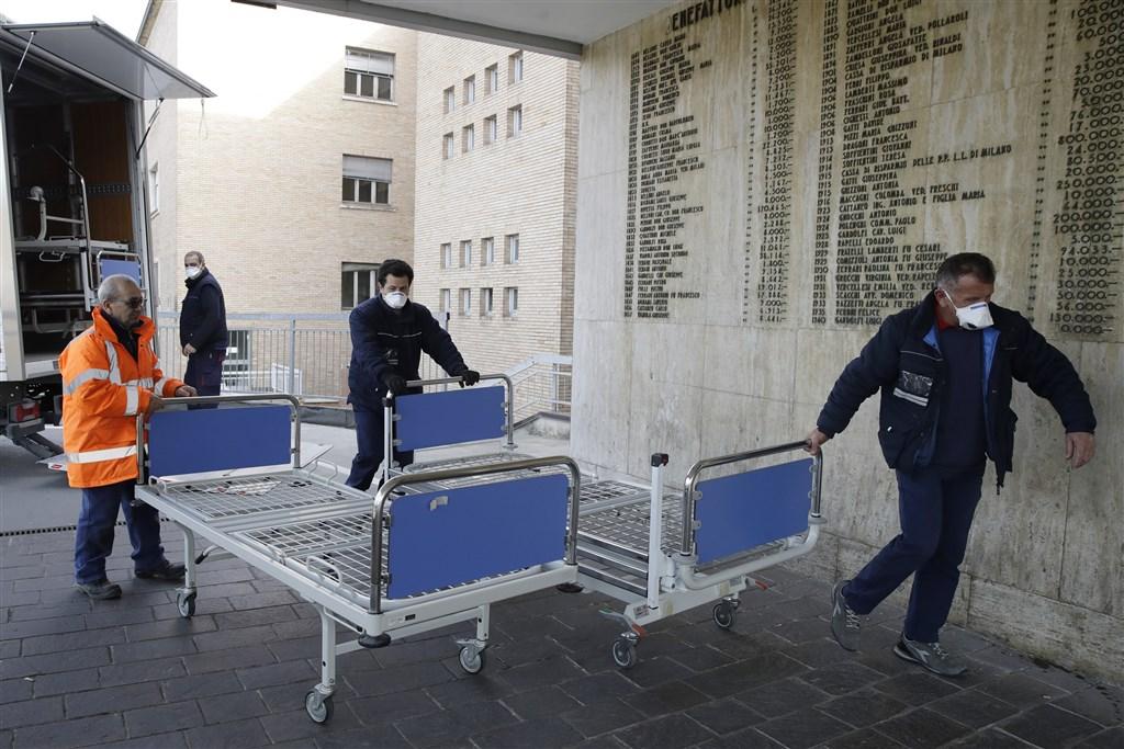 義大利新聞社21日報導,一名在北部城市巴多瓦的患者在感染冠狀病毒後死亡,成了義大利第一起罹患武漢肺炎的死亡病例。圖為義大利醫院工作人員搬運新病床。(美聯社)