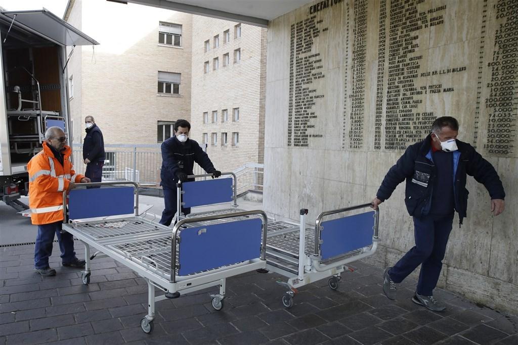 義大利武漢肺炎確診病例截至22日深夜案例已激增至79例,義大利政府非常憂心。圖為義大利醫院工作人員搬運新病床。(美聯社)