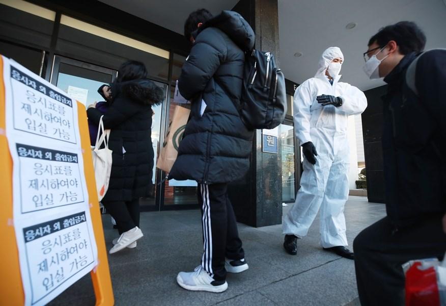 韓國政府23日將武漢疫情預警上調至最高等級「嚴重」,並強化應對措施。圖為韓國會計師考試試場檢疫人員引導考生進入考場。(韓聯社提供)