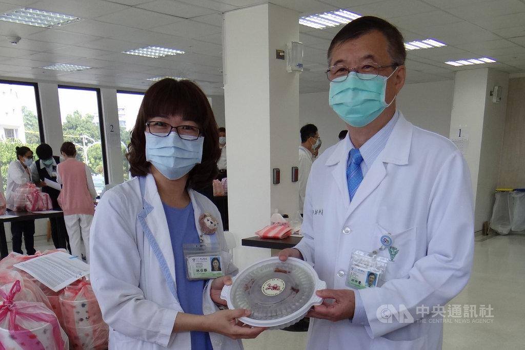 奇美醫學中心獲東成醬油公司捐贈5000份豬腳麵線與茶葉蛋,院長邱仲慶(右)24日將首批暖食轉發給第一線的醫護人員。中央社記者楊思瑞攝 109年2月24日