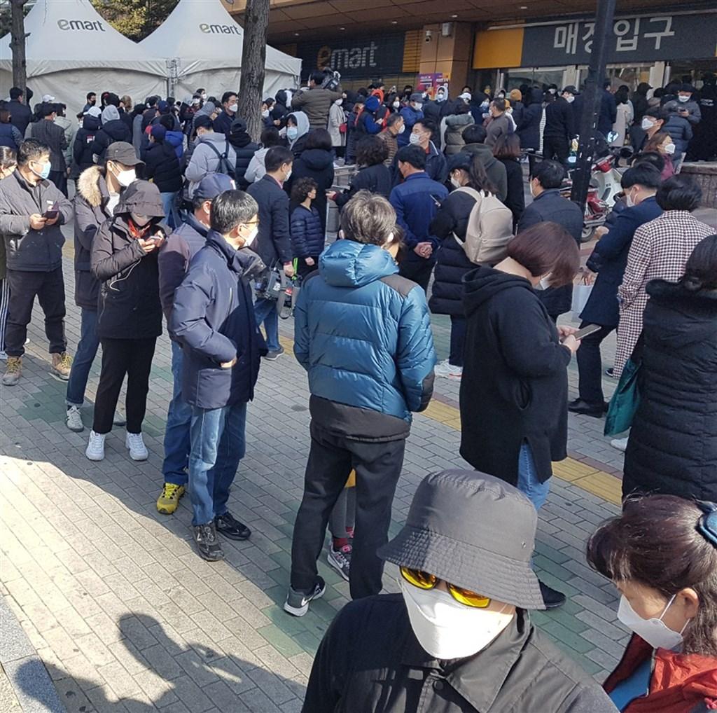 武漢肺炎疫情升溫,大邱市街道出現搶購口罩人潮。圖為大邱民眾24日排隊購買口罩。(韓聯社提供)