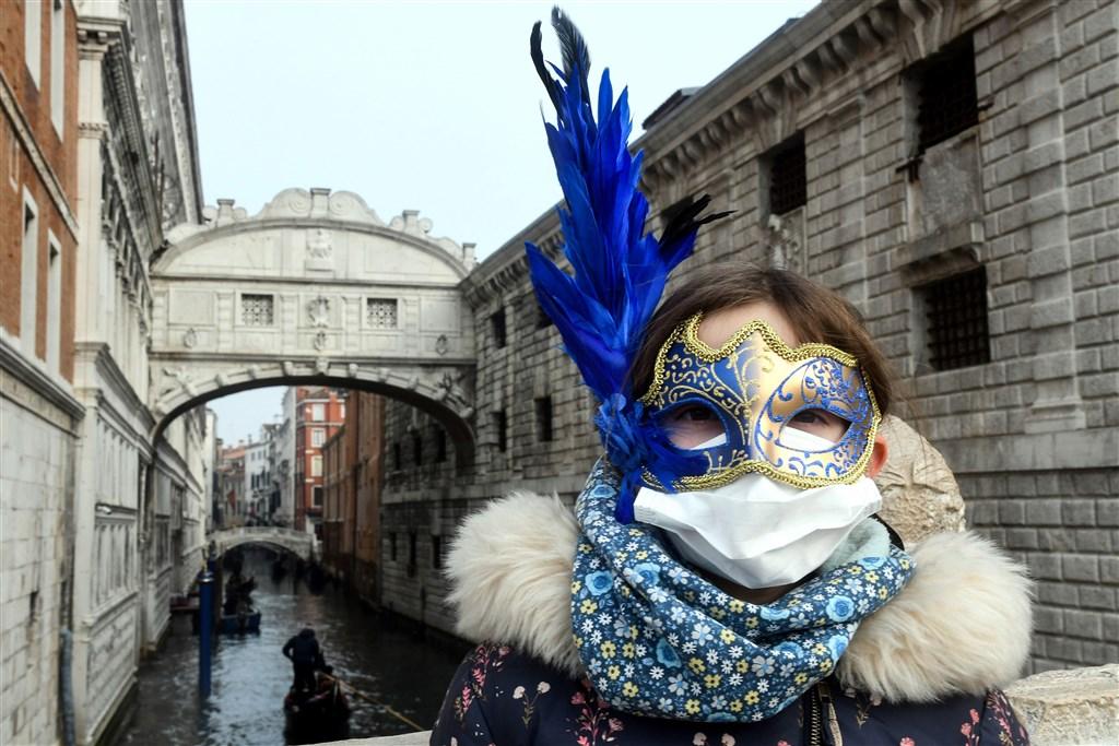 因應義大利武漢肺炎病例數快速攀升,指揮中心25日宣布,即日起提升義大利旅遊疫情建議至第二級警示。圖為一名戴着口罩的遊客在威尼斯嘉年華期間訪問威尼斯。(法新社提供)