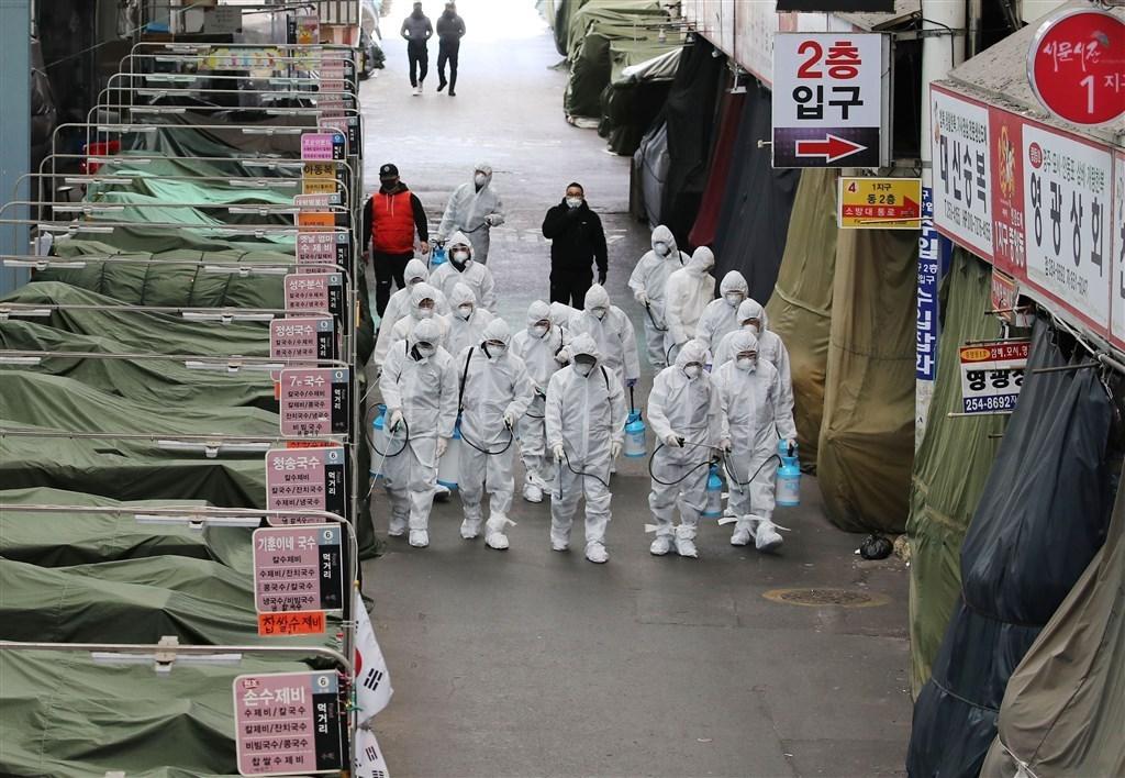 韓國執政黨發言人洪翼杓26日建議,為因應武漢肺炎,政府應在大邱市採取「最大程度封鎖」,但隨即引來反彈。圖為韓國防疫人員在市場噴灑消毒劑。(法新社提供)