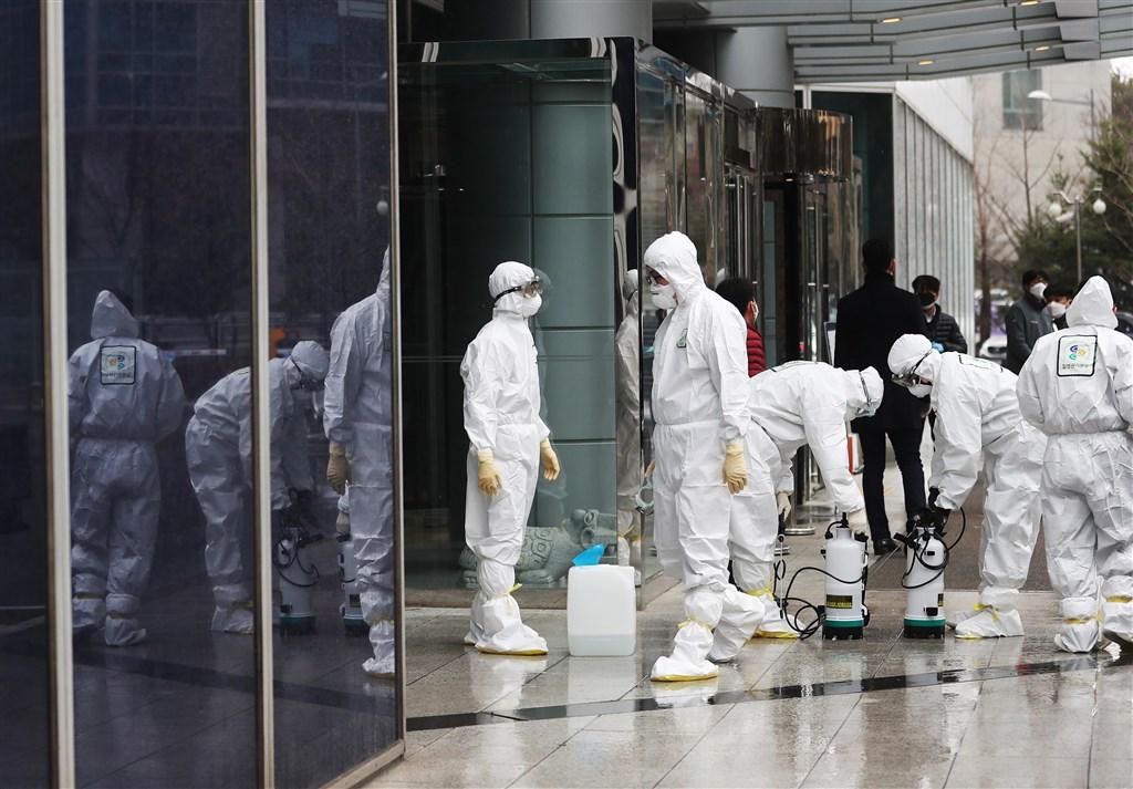 韓國的武漢肺炎確診累計病例26日增至4位數,有關當局通報新增169例,總計1146例確診。圖為防疫人員在大樓進行消毒。(韓聯社提供)