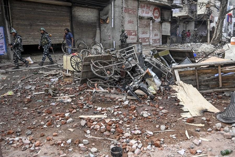 印度首都新德里因公民法修法,連日爆發印度教徒和穆斯林間暴力衝突,警方已逮捕514人。圖為新德里街頭可見被焚燒的自行車,衝突現場散落磚頭與石塊。(法新社提供)