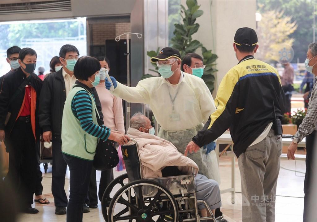 因應武漢肺炎疫情,台北榮民總醫院嚴格執行入院體溫測量,在入口處設置紅外線體溫感測儀,工作人員攔下體溫稍高的民眾,以額溫槍進行二次檢測。中央社記者裴禛攝 109年2月29日