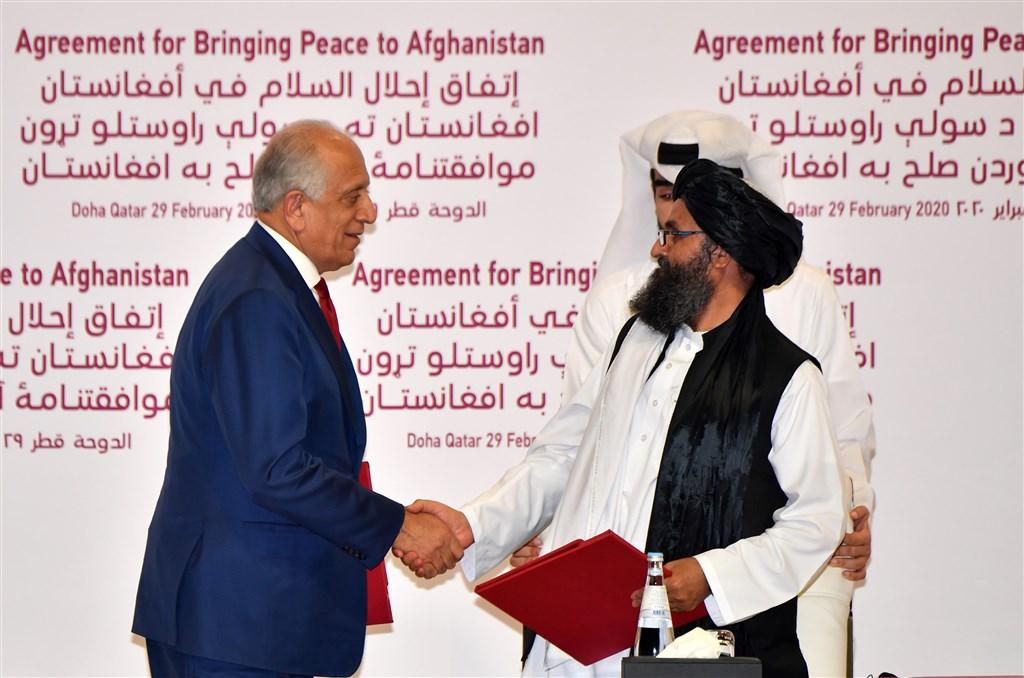 美國特使哈里札德(左)和塔利班創建元老之一巴拉達(前右)29日簽署和平協議後握手。(法新社提供)