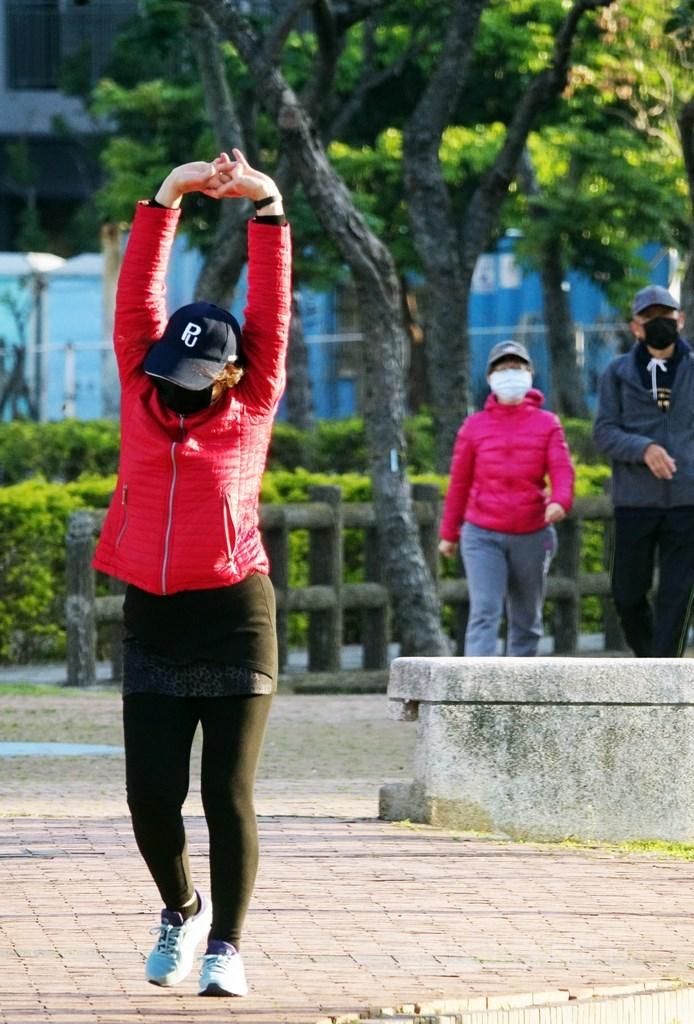 氣象局指出,1日北台灣高溫約24、25度,其他地方仍可達26至30度,下午後受東北季風增強影響,北台灣逐漸轉涼。圖為民眾晨起運動不忘戴上口罩。(中央社檔案照片)