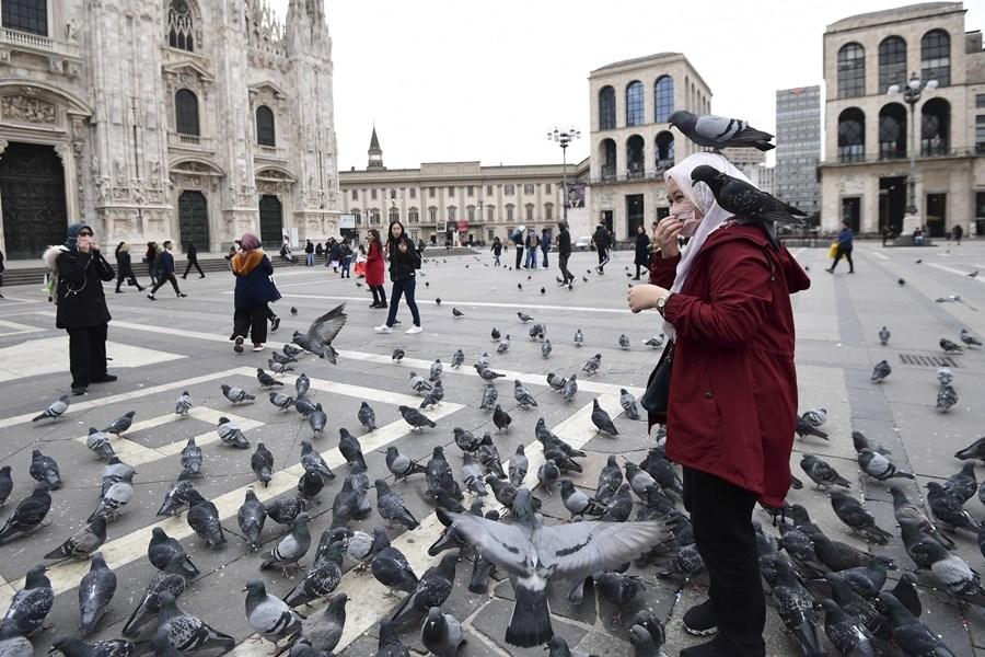 義大利疫情短短11天衝破2500例,成為歐洲主要「病毒輸出國」。圖為米蘭民眾在廣場配戴口罩。(法新社提供)
