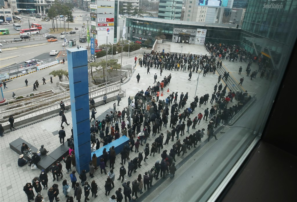 韓國政府5日宣布將提高公賣口罩占整體產量比重至8成,且每人每週僅限購買2片。圖為首爾民眾排隊等買口罩。(韓聯社提供)