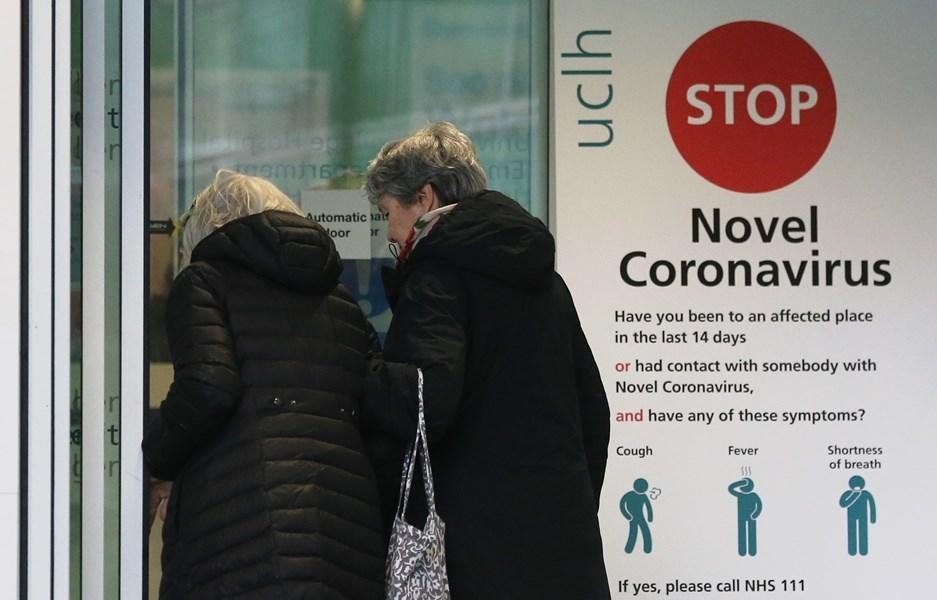 世界各地武漢肺炎確診病例數6日超出10萬起,其中英國和瑞士分別增加到163起和210起。圖為倫敦一所醫院外衛教看板。(法新社提供)