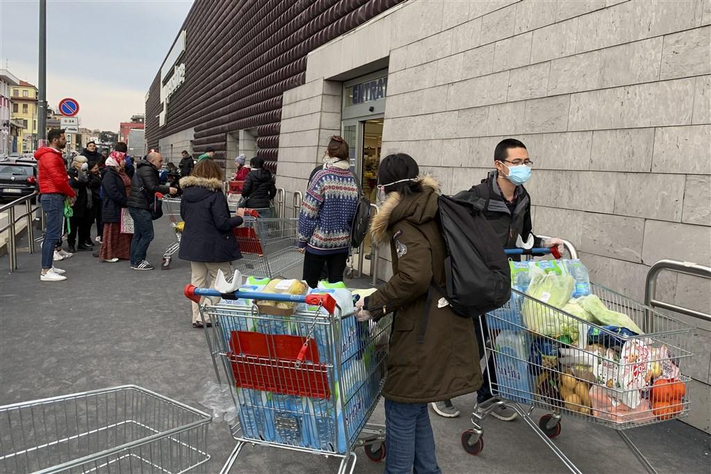 義大利總理孔蒂9日晚間宣布,將封鎖令範圍擴至全義大利。圖為8日倫巴底一間購物中心民眾排隊進入購物。(法新社提供)