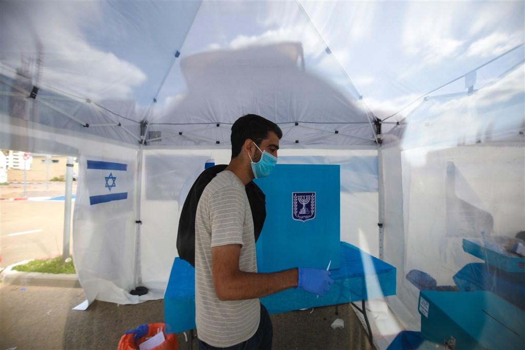 以色列總理尼坦雅胡9日表示,為預防武漢肺炎疫情擴散,將要求任何從海外入境人士自主隔離14天。圖為2日接受隔離的以色列民眾前往指定地點投票。(安納杜魯新聞社提供)