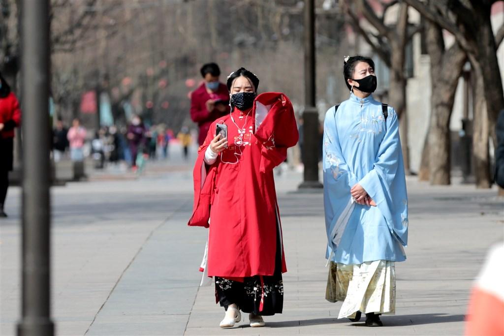 中國國家衛生健康委員會官網通報,13日武漢肺炎新增確診病例11例,其中7例為境外輸入,首度躍居最大來源。圖為西安民眾穿漢服戴口罩出遊。(中新社提供)