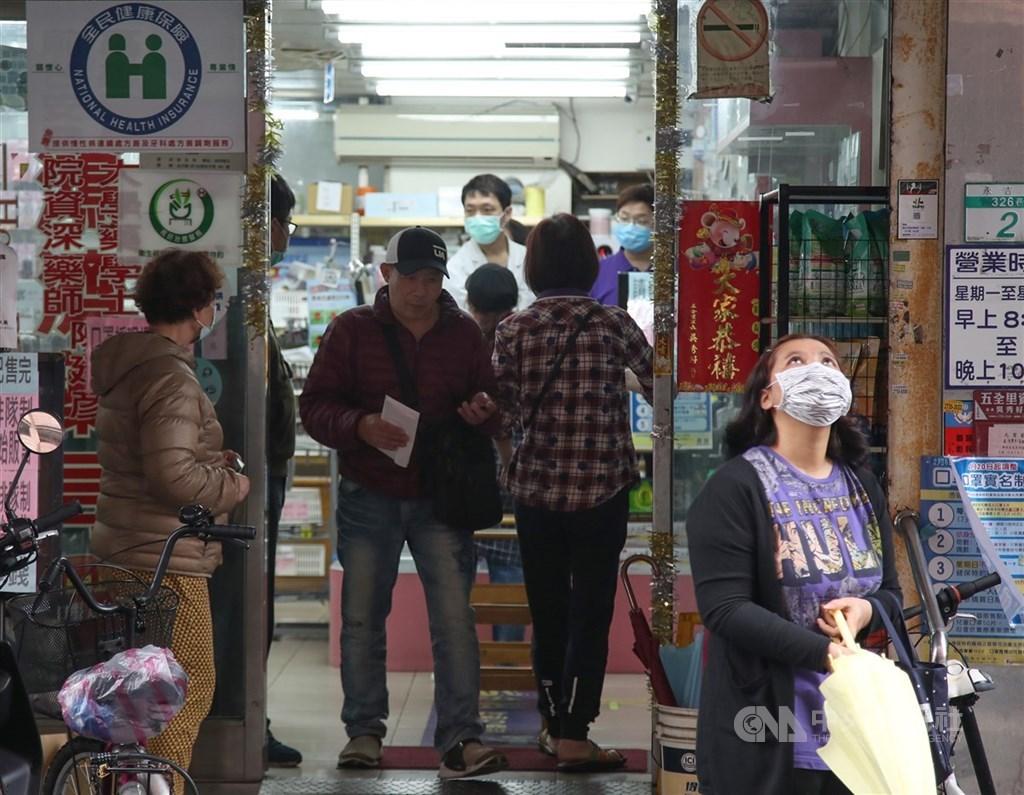 中央流行疫情指揮中心19日宣布,口罩實名制2.0預購第二輪將在25日開始,預購後4月2日領取。圖為民眾在藥局外排隊買口罩。(中央社檔案照片)