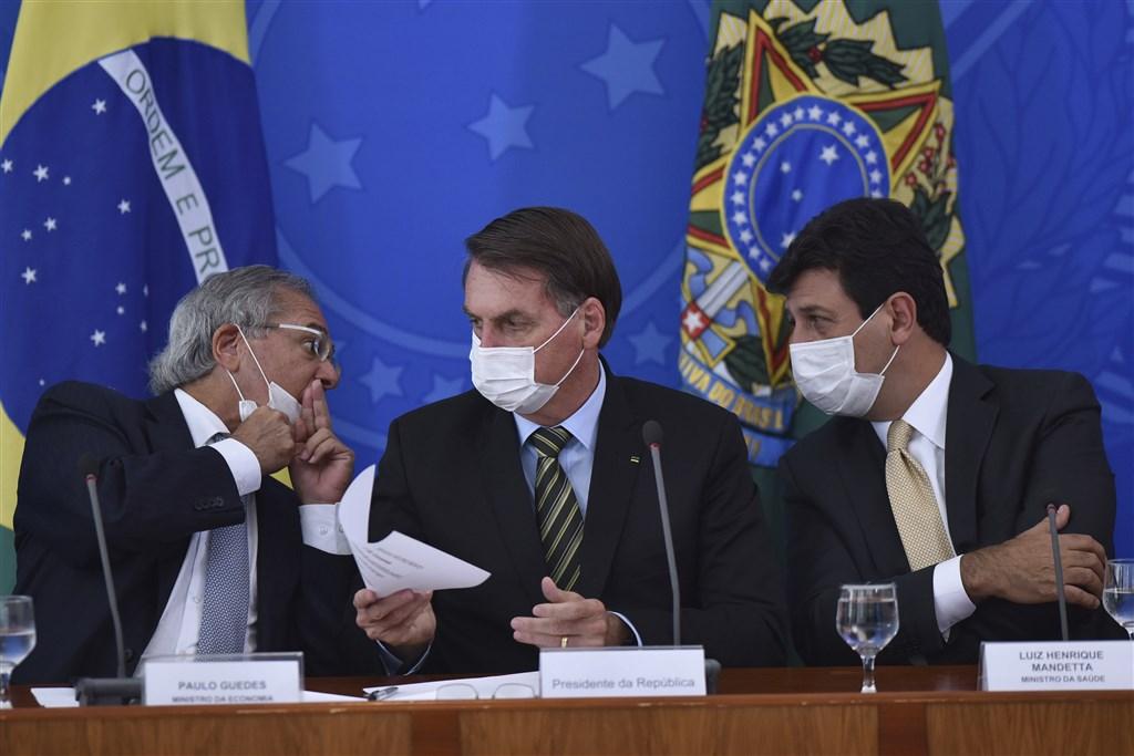 武漢肺炎在巴西蔓延,日前陪同巴西總統波索納洛(中)訪美的22位隨行人員已17人確診,18日波索納洛與多位部長戴口罩出席記者會,祭出新的防疫措施。(美聯社)