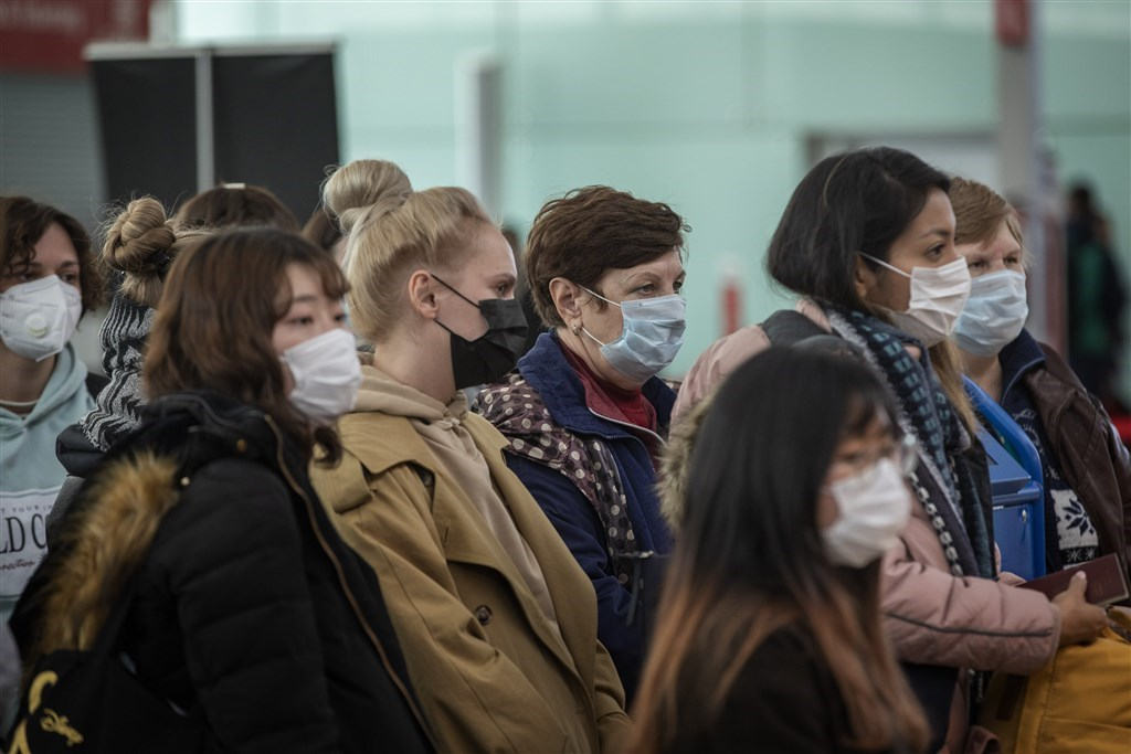 武漢肺炎延燒,已經造成全球近25萬人確診,1萬多人死亡。圖為西班牙巴塞隆納機場旅客戴著口罩。(美聯社)