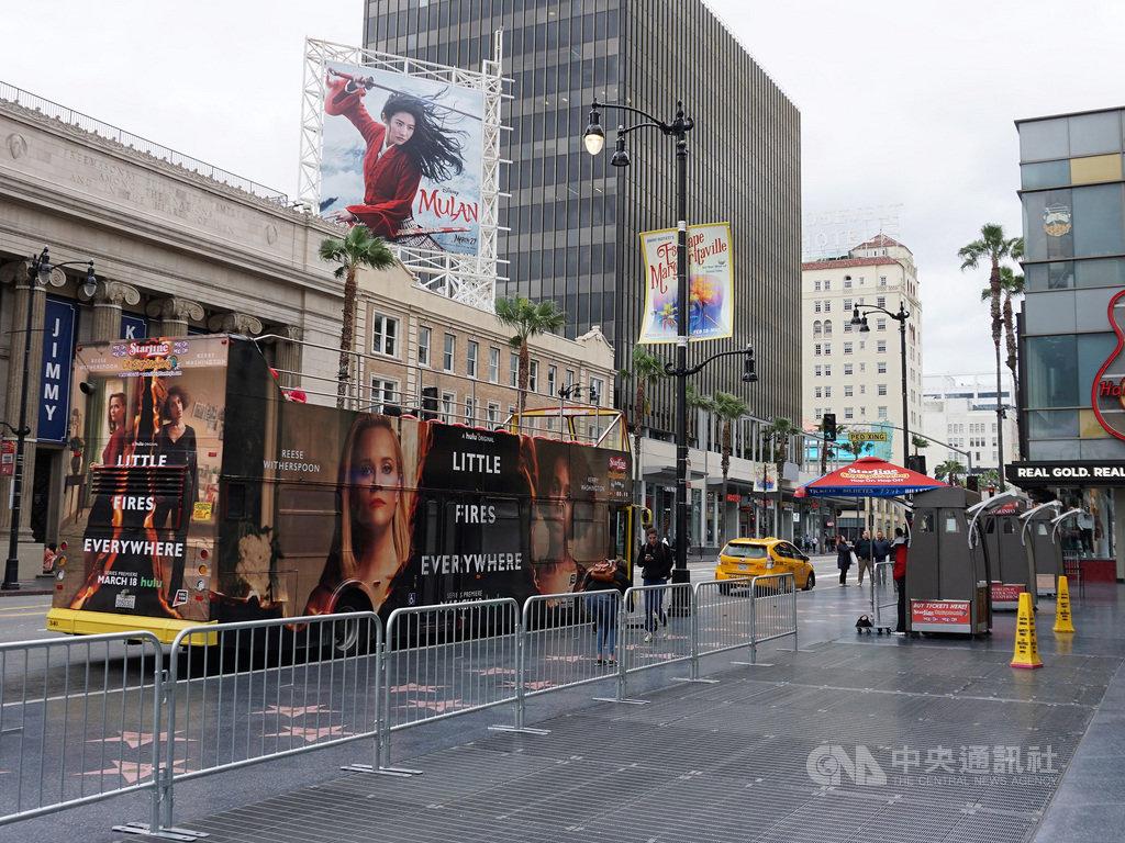 武漢肺炎疫情擴大,美國洛杉磯的觀光景點好萊塢星光大道顯得冷清,導覽巴士沒人坐,看板上的電影「花木蘭」延後上映。中央社記者林宏翰洛杉磯攝 109年3月22日