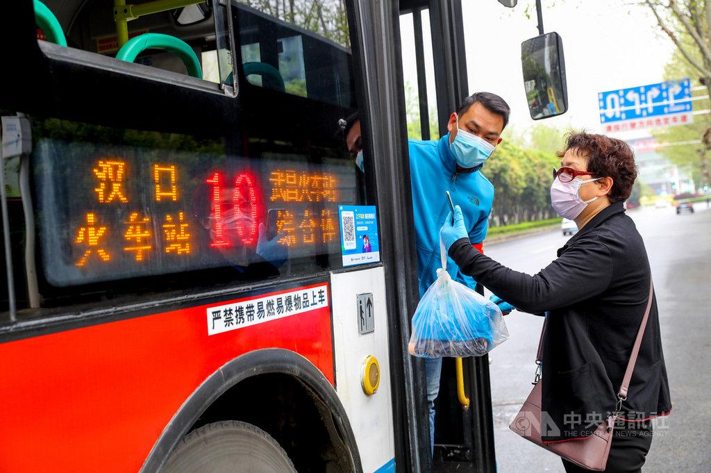 湖北省25日更新縣市疫情風險等級評估,將疫情最嚴重的武漢市降為中風險,這也代表中國疫情高風險縣市歸零。圖為武漢多線公車25日復駛,乘客須用手機掃碼實名登記上車。(中新社提供)中央社 109年3月25日