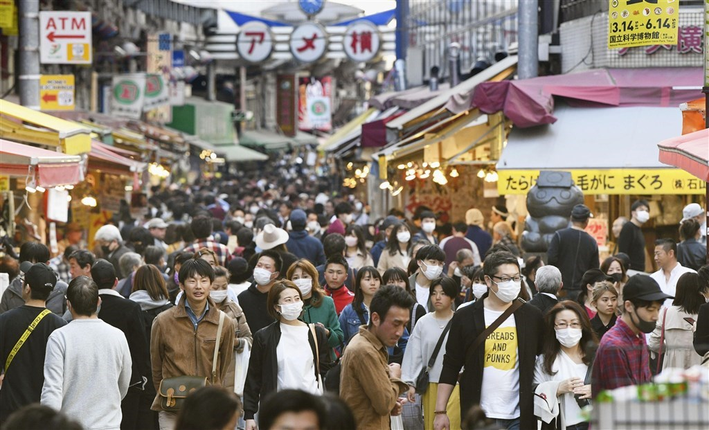 日本境內25日新增96起武漢肺炎確診感染案例。圖為東京民眾戴口罩逛阿美橫商店街。(共同社提供)